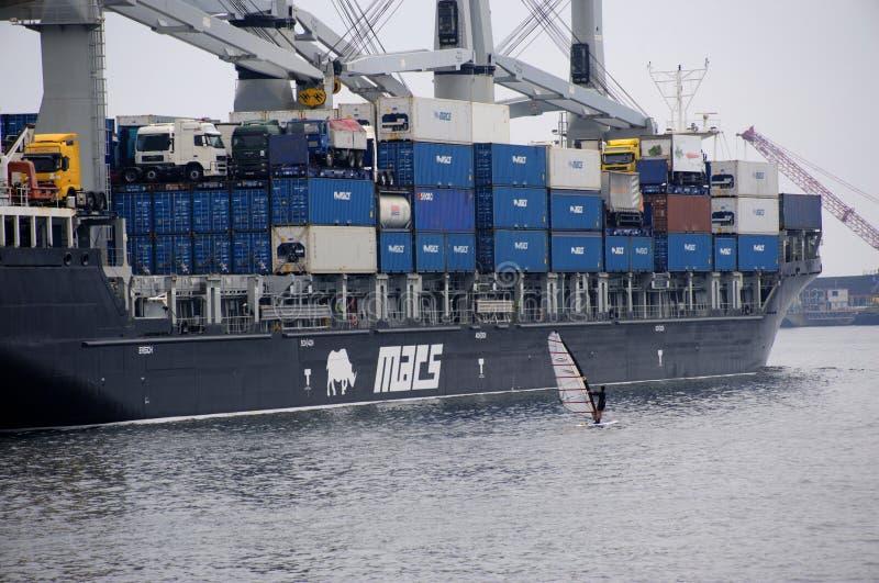 与巨型集装箱船对比的风帆冲浪者 免版税库存图片