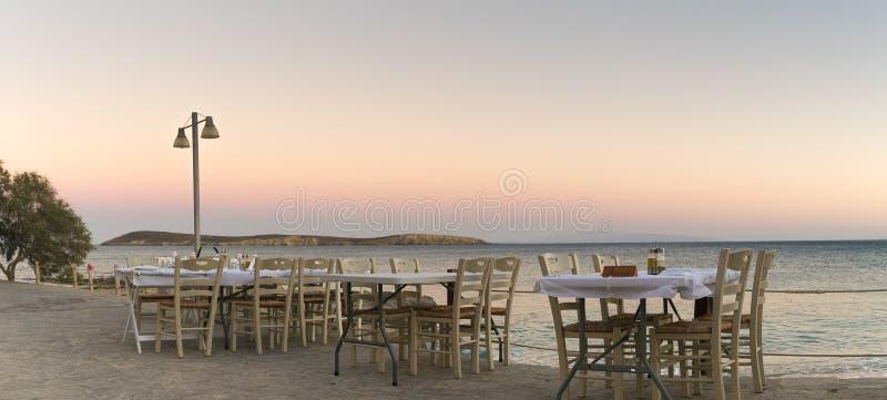 与希腊小酒馆的美好的环境准备好帕罗斯岛的海岛的欢迎地方人和游人晚餐的 免版税库存照片