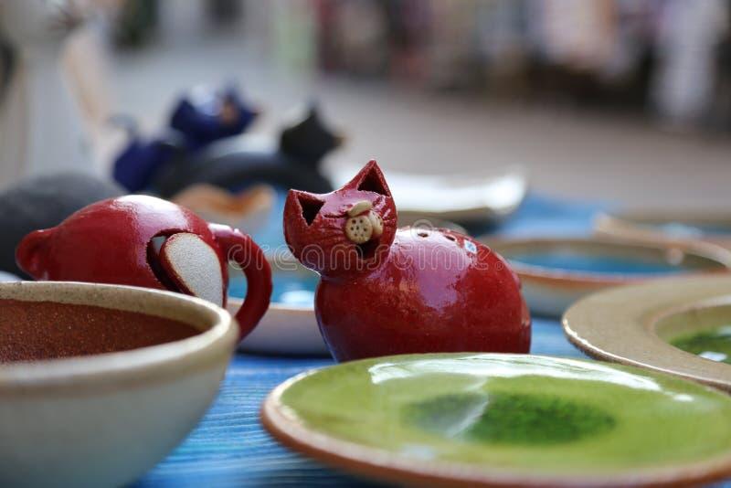 与希腊手工制造纪念品的架子-五颜六色的陶瓷杯子和板材有猫头鹰、动物和花的图片的 免版税库存图片
