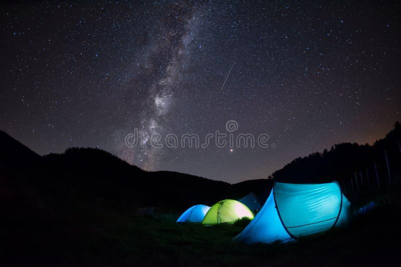 与帐篷照亮夜的,山的银河在Perseid流星雨冒险 库存图片
