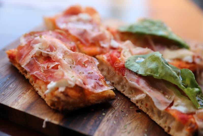 与帕尔马火腿沙拉火箭和巴马干酪的比萨在黑暗的木背景关闭 烹调意大利语的食品成分 库存图片