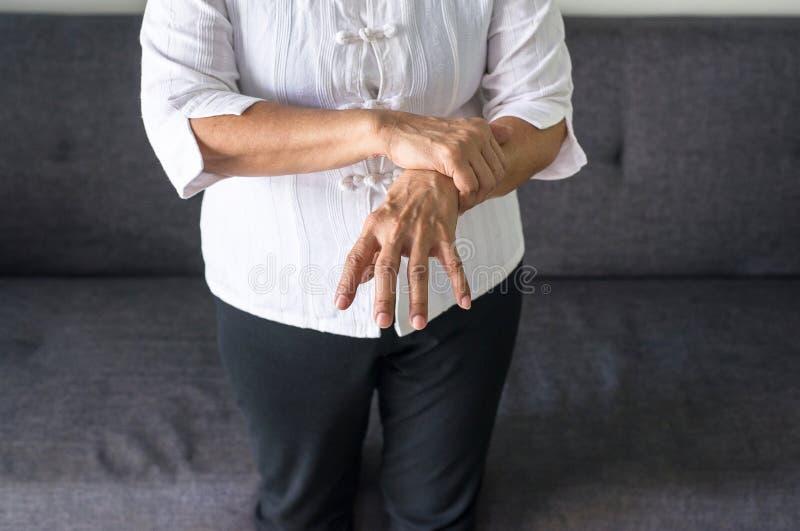 与帕金森病症状的年长女性痛苦 库存图片