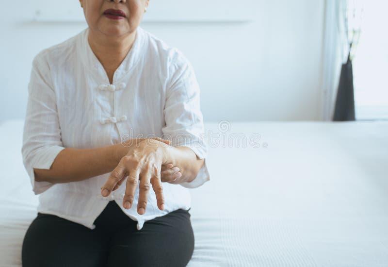 与帕金森病症状的年长妇女痛苦在手边 免版税库存照片