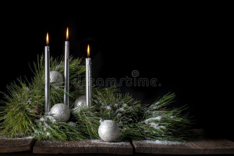 与常青树和雪的银色圣诞节蜡烛 免版税图库摄影