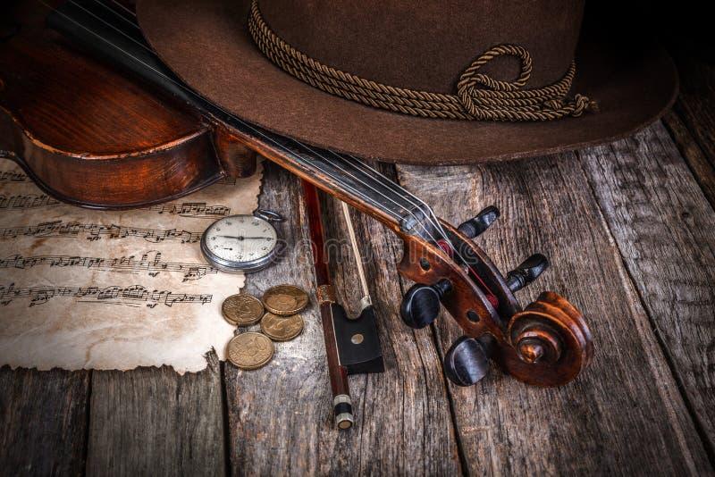 与帽子、小提琴和硬币的静物画 库存照片