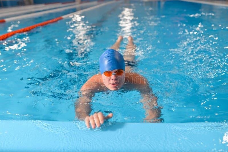 与帽子和风镜的专业人游泳在水池 免版税库存照片