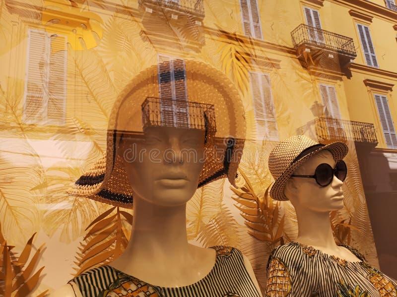 与帽子的母时装模特在商店窗口里 库存照片