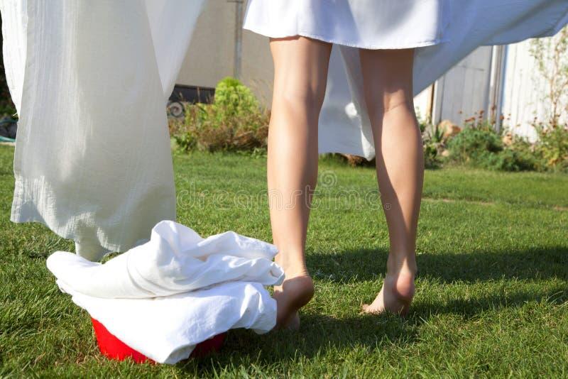 与干净的亚麻布的塑料水池在绿草 腿在背景中拔 图库摄影