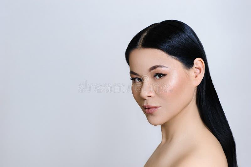 与干净的新鲜的皮肤、裸体构成、整容术、医疗保健、秀丽和温泉的美丽的亚洲妇女面孔 免版税库存图片