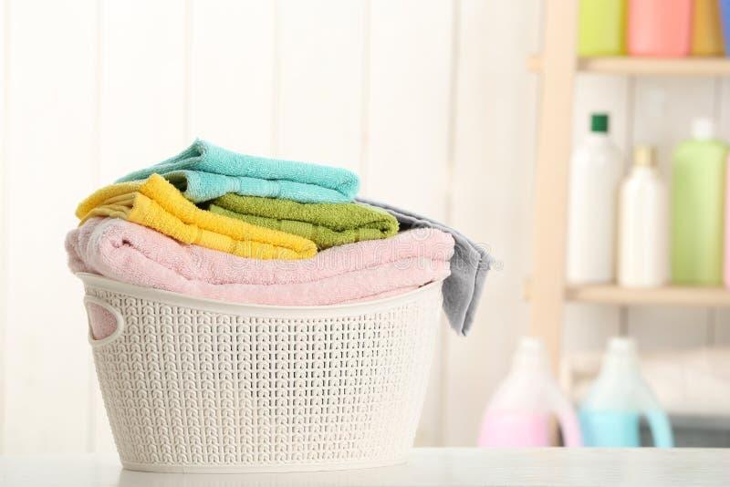 与干净的洗衣店的篮子在桌上在家 免版税库存照片