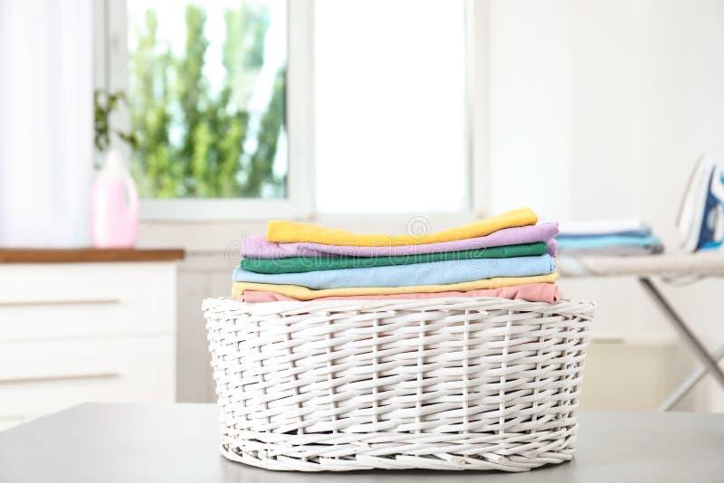 与干净的洗衣店的篮子在桌上 免版税库存图片