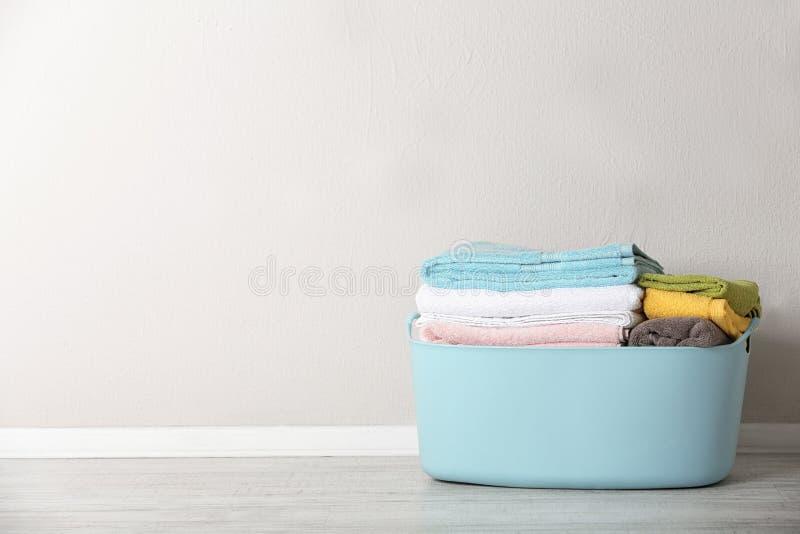 与干净的洗衣店的篮子在颜色墙壁附近的地板上 免版税库存照片
