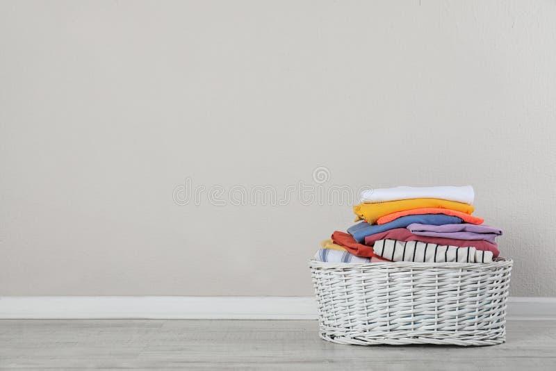 与干净的衣裳的柳条洗衣篮在轻的墙壁附近的地板上 免版税库存图片