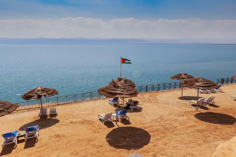 与干净的黄沙和沙滩伞的美丽的海滩在死海岸 库存图片