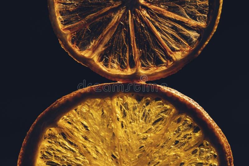 与干切片的静物画桔子,在黑背景的柠檬 免版税库存照片