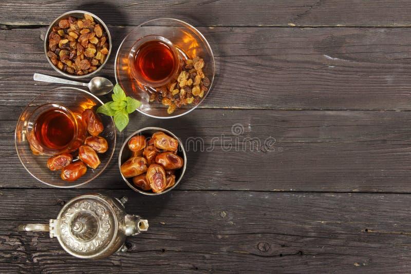 与干旱时期的传统阿拉伯,土耳其语赖买丹月在一张木黑桌上的茶和葡萄干 ramadan 土耳其新鲜的茶与日期 图库摄影