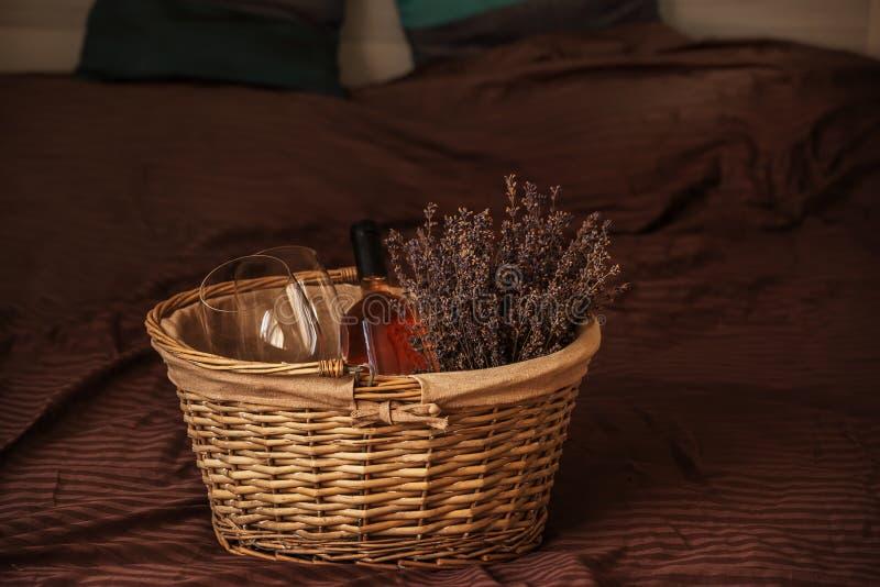 与干淡紫色花、玻璃和一个瓶的柳条筐在床上的酒 免版税库存图片