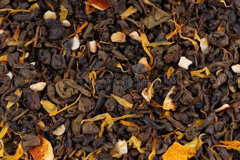 与干燥花和糖煮的橙色背景的绿色锡兰茶 库存照片