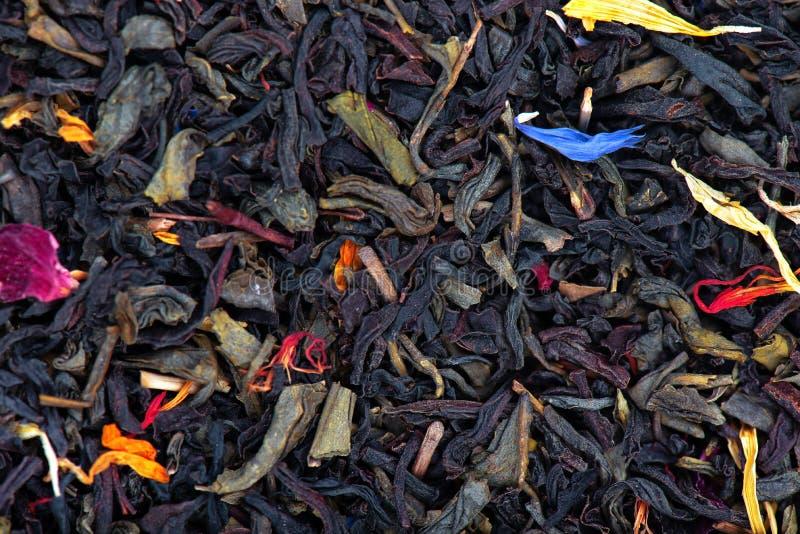 与干燥花-金盏草、玫瑰和矢车菊瓣,背景的黑和绿色锡兰茶 免版税库存照片
