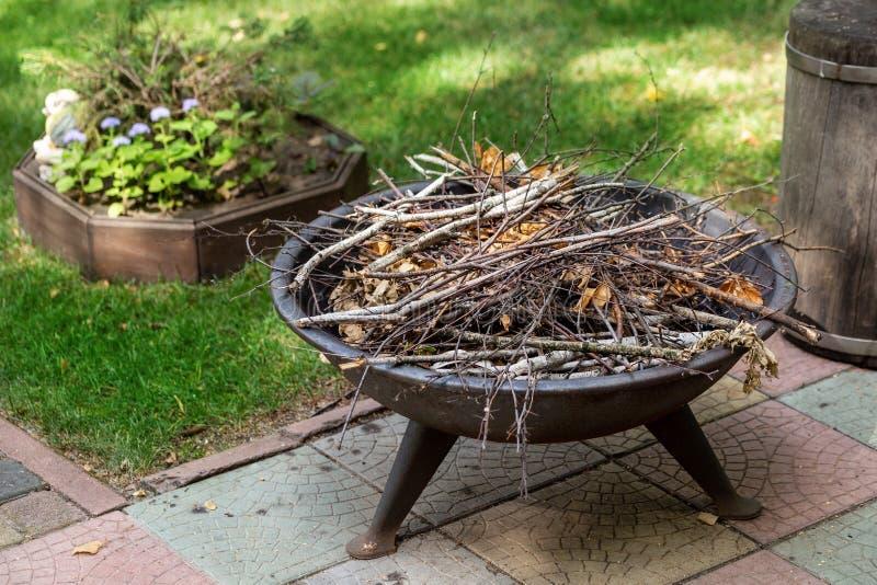 与干燥草丛的便携式的铁壁炉在夏天村庄后院  为平衡营火故事准备的篝火 库存图片