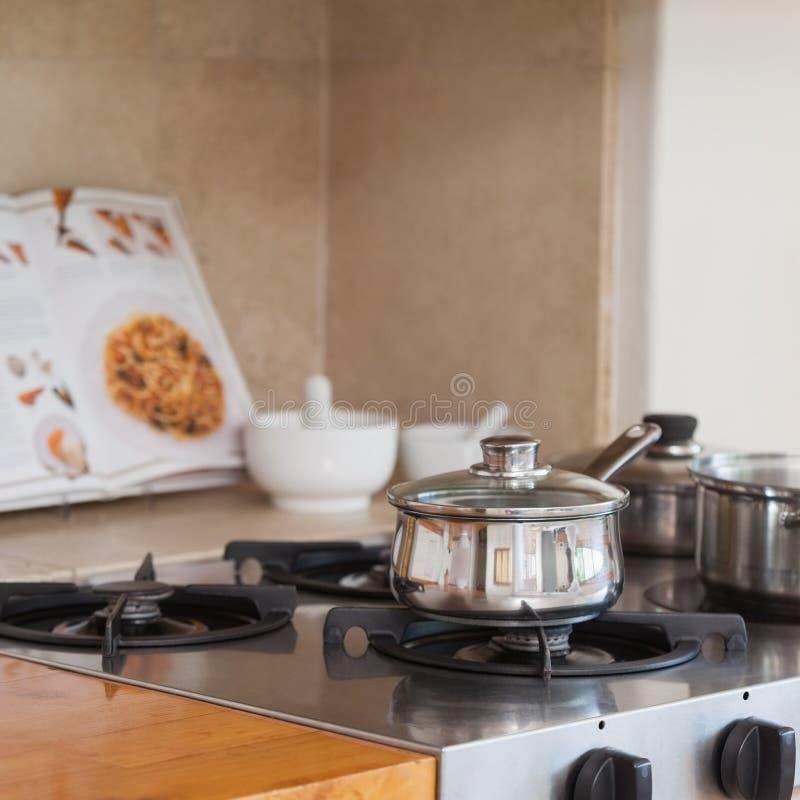 与平底深锅和食谱书的火炉上面 免版税图库摄影