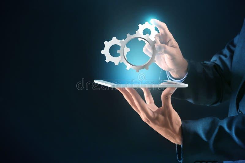 与平板电脑的商人和在黑暗的背景的数字大齿轮 互联网和技术支持服务的概念 免版税库存图片