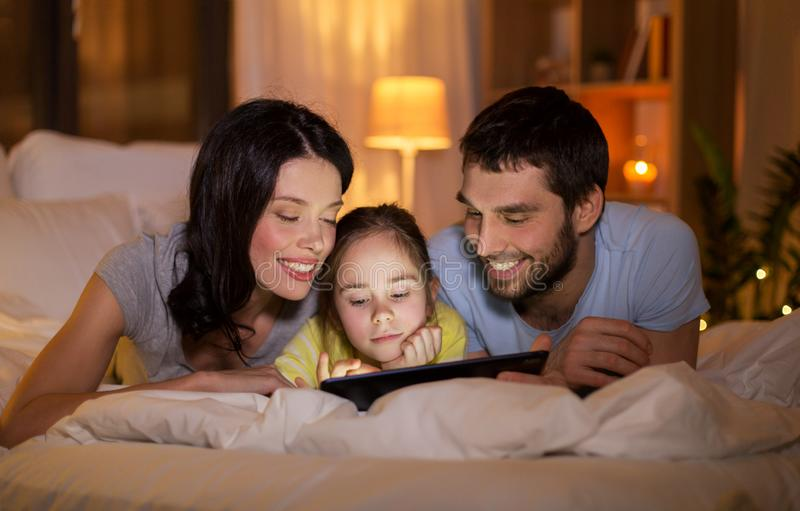 与平板电脑的家庭在床上在晚上在家 免版税库存图片
