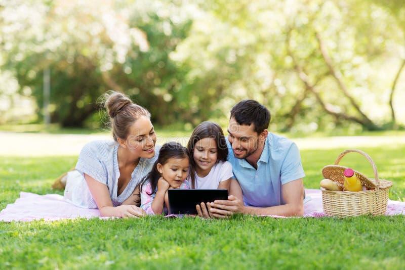 与平板电脑的家庭在野餐在夏天公园 免版税库存图片