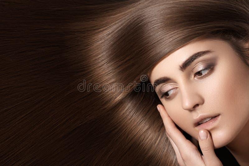 与平直的黑发的肉欲的妇女模型 发光的长的健康发型 图库摄影