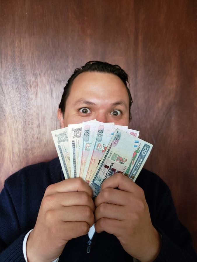 与年轻人和拿着危地马拉钞票的情感表示的面孔 免版税库存图片