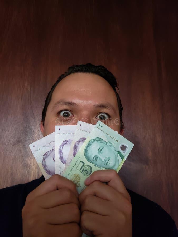 与年轻人和拿着新加坡钞票的情感表示的面孔 库存图片
