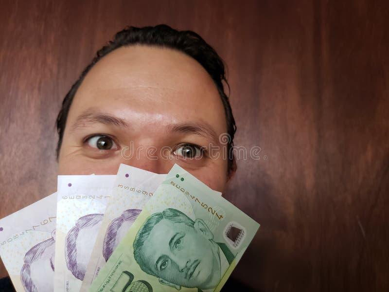 与年轻人和新加坡钞票的情感表示的面孔 库存照片