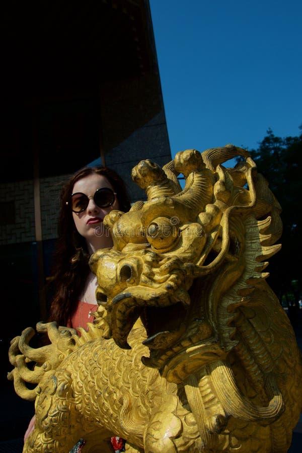 与年轻白色女性旅游噘嘴的金黄中国龙雕象 免版税库存照片