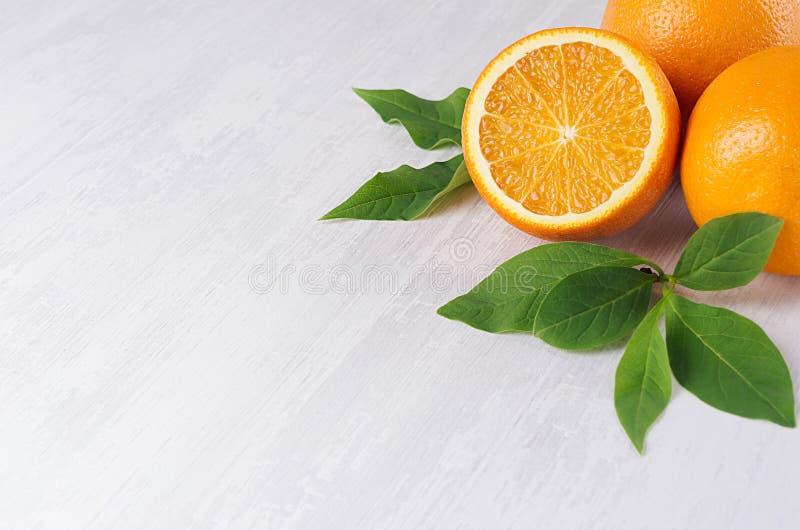 与年轻绿色叶子和圆的切片特写镜头的水多的桔子在软的白色木背景 库存图片