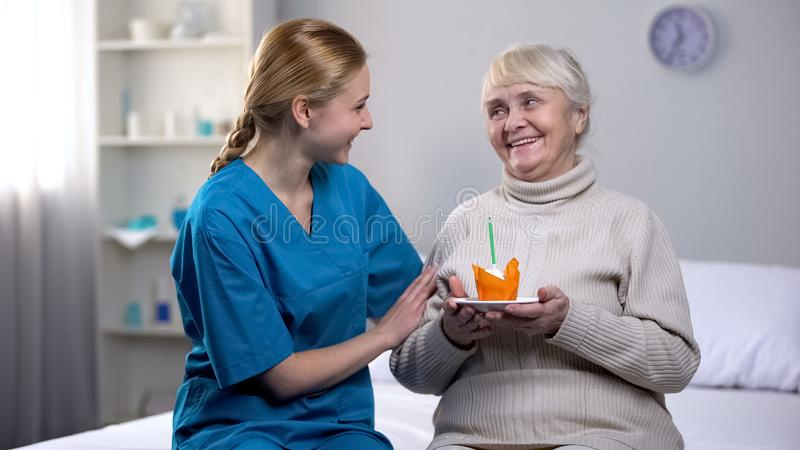 与年长夫人藏品蛋糕的志愿庆祝的生日,病人护理 库存图片