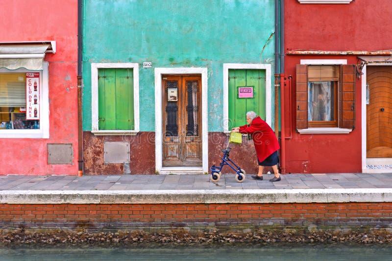 与年长妇女步行的美丽如画的都市风景与沿水运河的一位推车家庭教师在有backg的Burano海岛 免版税库存照片