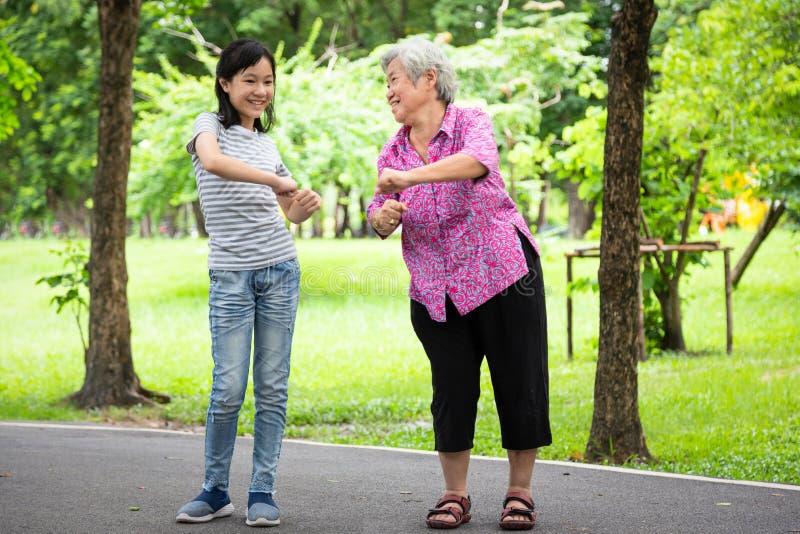 与年长妇女的愉快的亚洲小孩女孩微笑和锻炼在室外公园,孙女,资深祖母跳舞, 免版税库存照片