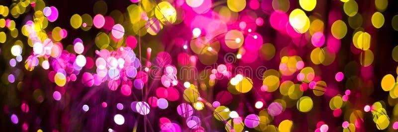 与幻想bokeh纹理紫色氖和金黄颜色的抽象背景 时兴的圣诞节背景 免版税库存图片