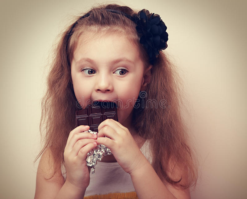 与幽默看起来的想法的孩子吃巧克力的 葡萄酒 库存图片