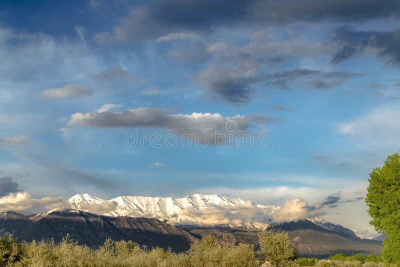 与庄严雪的风景自然视图锐化了山在多云天空蔚蓝下 图库摄影
