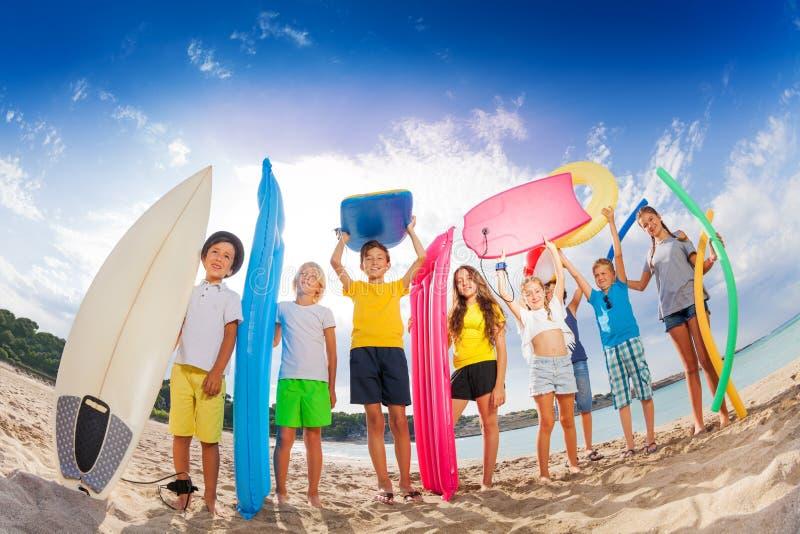 与床垫水橇板的许多孩子在海滩 库存照片