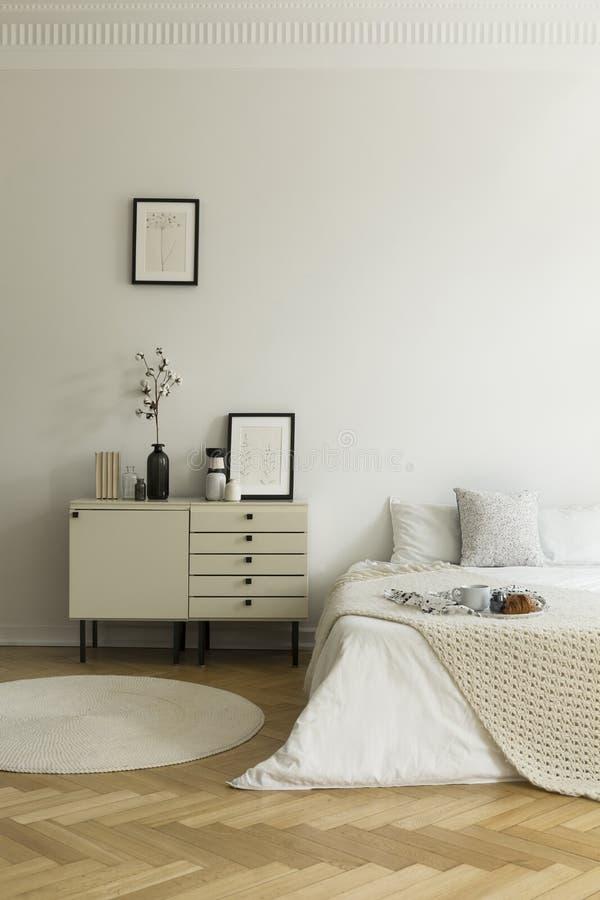 与床的单色,白色卧室内部和nightstand 在床上供应的早餐 实际照片 免版税库存照片
