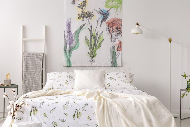 与床的淡色卧室内部在绿色植物样式白色亚麻布穿戴了 在花和鸟绘的织品在backg 库存照片