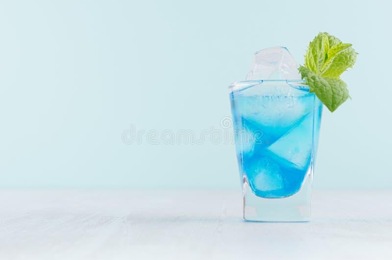 与库拉索岛,冰块,在misted小玻璃的绿色薄菏的魅力热带水果蓝色鸡尾酒在现代薄荷的颜色内部 库存图片