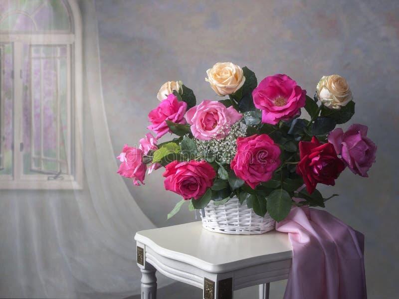 与庭院多彩多姿的玫瑰篮子的静物画在桌上的 免版税库存照片