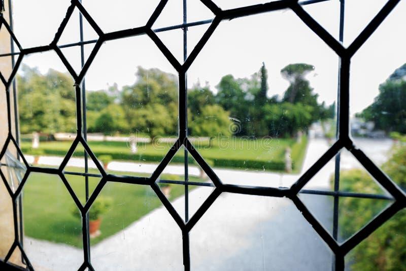 与庭院的老行间空格特别大的彩色玻璃 免版税库存照片