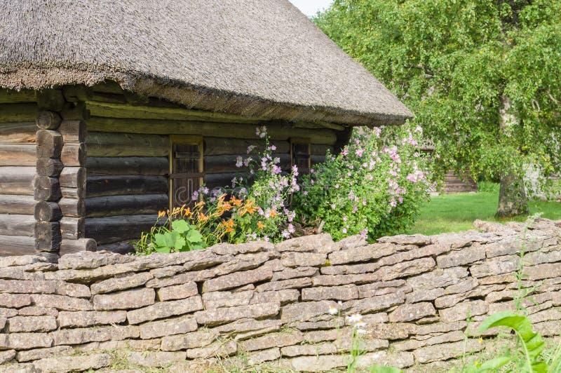 与庭院花和石灰石篱芭的农村原木小屋 免版税库存照片
