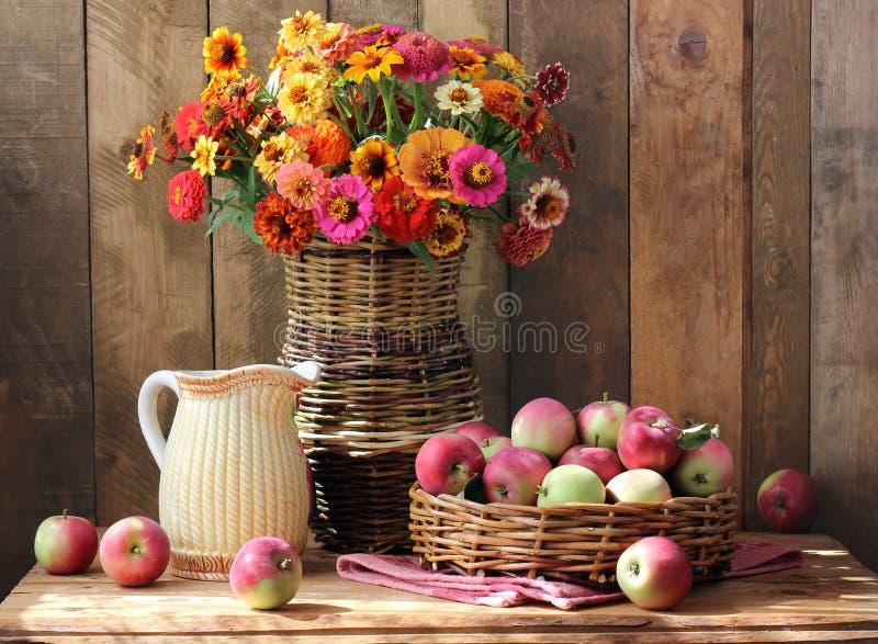 与庭院花和苹果的静物画在篮子 免版税库存图片