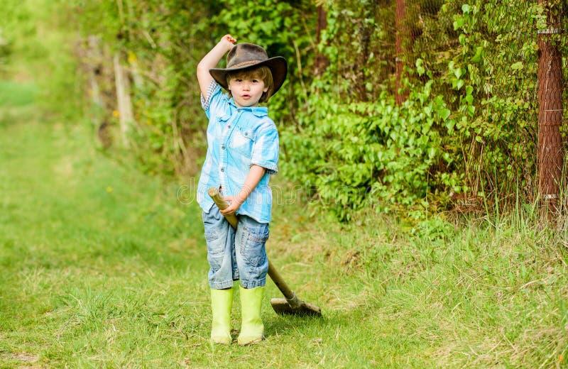 与庭院铁锹,春天的愉快的儿童农夫戏剧 r Eco?? 夏天活动 获得小孩子的花匠乐趣 免版税库存图片