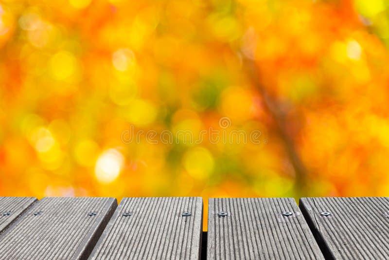 与庭院bokeh的五颜六色的颜色的空的木台式创造的 免版税库存图片